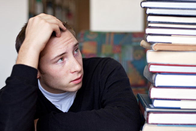 Desktop a frustrated and stressed out student looks up at the high pile of textbooks he has to go through to do his homework sttlftcsj